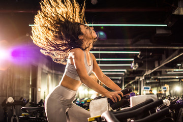 Side view of attractive young woman with long hair in the air during during cycling training in gym