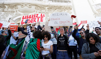 People take part in a protest against Algerian President Abdelaziz Bouteflika seeking a fifth term in a presidential election set for April 18, in Tunis