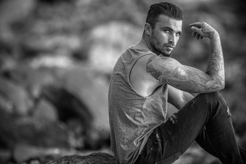Model Guy sitting on the rock at beach
