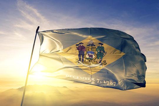 Delaware state of United States flag waving on the top sunrise mist fog
