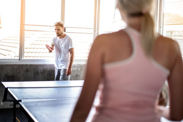 couples playing ping pong (table tennis) in gym