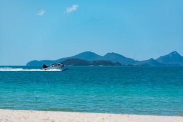 Wasserflugzeug beim Start mit Blick vom Strand