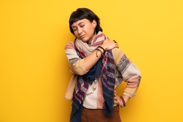 Young hippie woman over yellow wall suffering from pain in shoulder for having made an effort