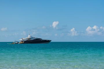 Motor-Yacht ankert vor einer Insel mit Blick vom Strand