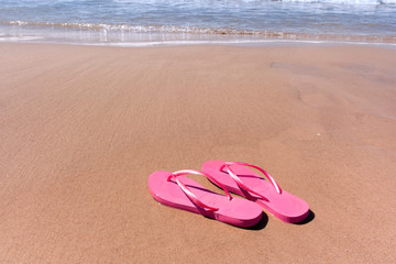 pink flip-flops on yellow sand at the water's edge on the beach