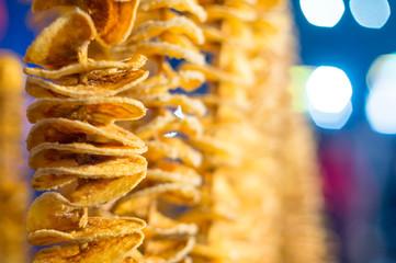 Potato spiral or tornado fried on skewer shot with low depth of feild