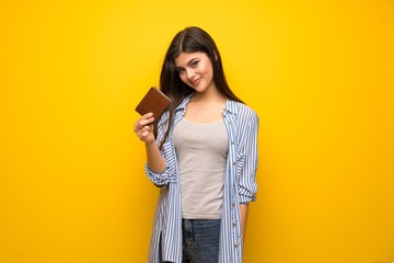 Teenager girl over yellow wall holding a wallet