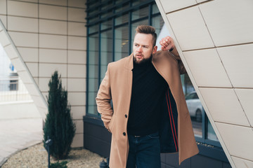 Young bearded man with modern hairstyle and trendy coat standing near business center