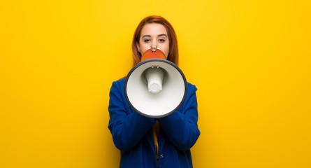 Young redhead woman with trench coat shouting through a megaphone
