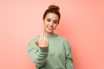 Young redhead woman with sweatshirt inviting to come with hand. Happy that you came