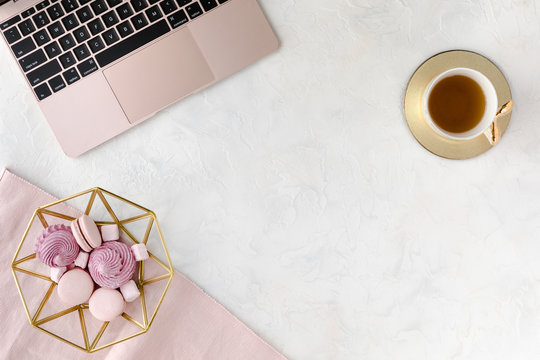 Stylish women's office desk, flat lay. Feminine workspace with, laptop, cup of herbal tea and dessert. Female table on white background. Flatlay, top view