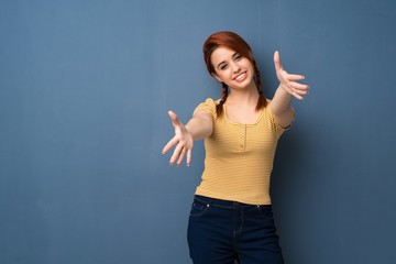 Young redhead woman over blue background presenting and inviting to come with hand