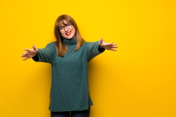 Woman with glasses over yellow wall presenting and inviting to come with hand