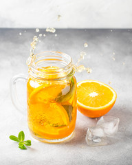 Cold tea with orange, mint and ice, sweet summer drink, refreshing lemonade, juicy cocktail. Spray, splash