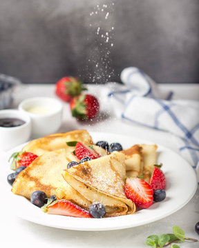 Thin pancakes with strawberries and blueberries, jam, condensed milk, delicious Breakfast. Russian traditional dessert for Shrovetide celebration (maslenitsa). French crepes
