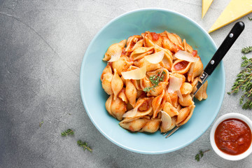 Pasta conchiglioni (conchiglie, shells) with tomato sauce, Parmesan cheese and thyme in a blue plate on a gray background. Delicious healthy vegetarian food, Italian cuisine