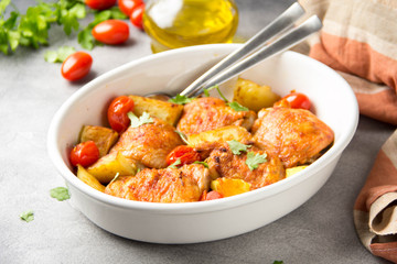Baked chicken thighs (legs) with crispy crust, potatoes and cherry tomatoes. Simple delicious homemade dinner, traditional meal. Everyday food cooked in oven