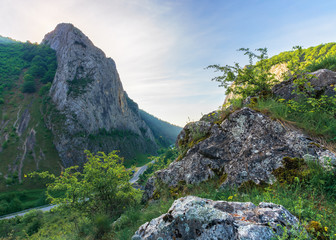 beautiful mountain landscape of romania. huge rocky formations on top of a hill. road winding down the valley. wonderful springtime scenery at sunrise