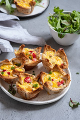 Egg muffins with peppers in a toast cup for breakfast brunch.