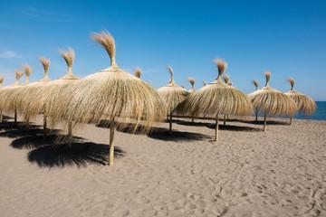 Grass umbrellas on a mediterranean resort beach.
