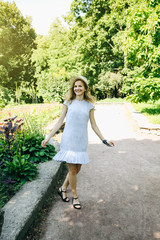 Beautiful girl in stylish hipster dress and hat is walking in the park. Summer happy photoshoot outdoors.