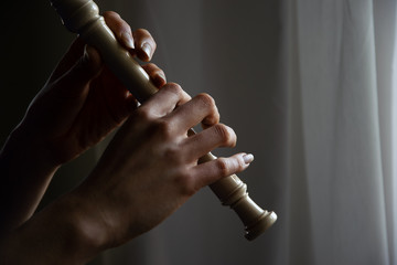 Close up of woman's hands playing a sweet flute.