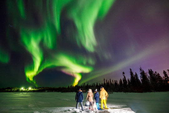 Company of friends tourist looks northern lights at edge forest
