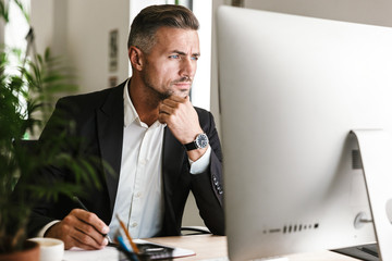 Image of confident businessman working in office and looking on computer