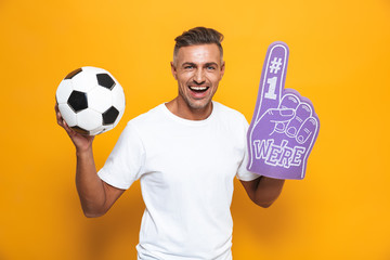 Image of beautiful man 30s in white t-shirt holding soccer ball and number one fan hand glove with finger raised while standing isolated
