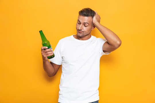 Image of drunk man 30s in white t-shirt holding bottle and drinking beer while standing isolated