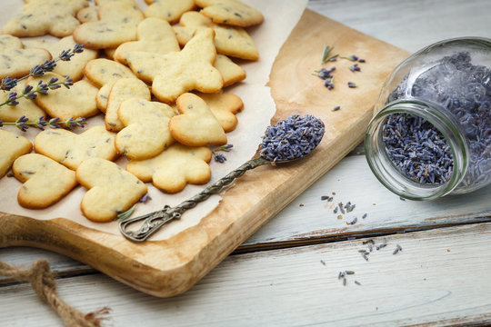 Lavender cookies on cutting board, on white baking paper
