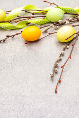 Easter eggs concept willow seals branches with polka dot satin ribbons. On a stone background, copy space.