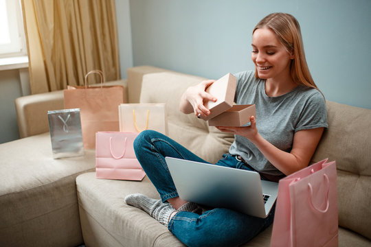 Online shopping at home. Young smiling shopper is unboxing her parcel and looking into, ordered and delivered by internet