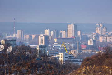 Early spring at sunny evening in warm weather. Industrial zone and residential areas Podin and northern suburbs Obolon in Kyiv on the right bank of the Dnipro River. Ukraine Mar. 6, 2019
