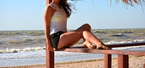 Young woman poses for a photographer at a photo shoot near the sea