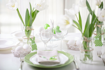 Decor and table setting of the Easter table with white tulips and dishes of green and white color. Easter decor in the form of Easter bunnies  green color with white polka dots.