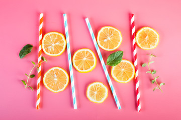 Colored straws and fresh lemon slices, mint leaves on a pink background