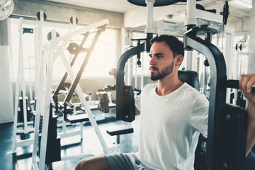 Handsome Man is Exercising With Pectoral Machine in Fitness Club.,Portrait of Strong Man Doing Working Out Calories Burning in Gym., Healthy and Fitness Lifestyle Concept.
