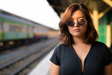 Young beautiful Asian tourist woman with sunglasses at the railway station