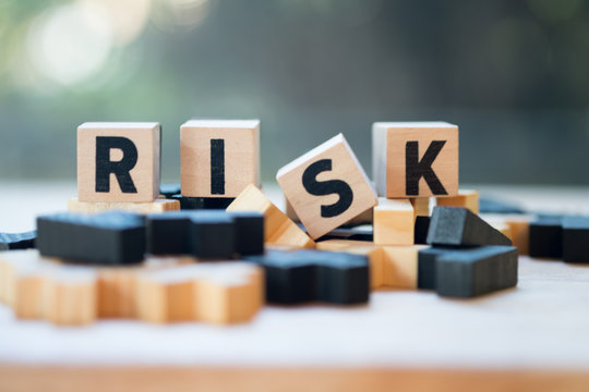 Cube wooden block with alphabet building the word RISK. Risk assessment