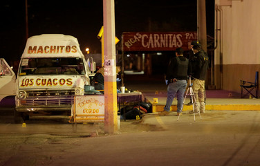 Members of the forensic team work at a crime scene where according to local media two men and a woman were killed when gunmen opened fire on Saturday at a street in Ciudad Juarez