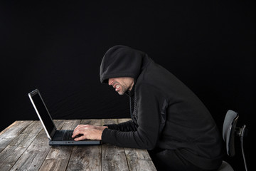 Fototapeta hacker in black hoody with laptop