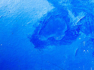 Old, peeling blue paint on the wall is painted on top of a darker blue paint.