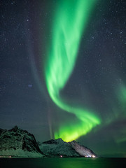 beautiful northern light over snow covered mountain landscape in arctic norway, vertical shot