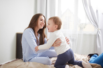 Young beautiful mother and her little son dressed in pajamas have fun on the bed in the light cozy bedroom