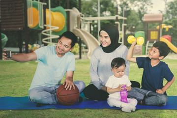 Happy family sitting at the playground