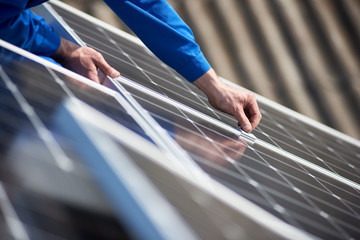 Male engineer in blue suit installing solar photovoltaic panel system. Close up view of electrician hands mounting blue solar module on roof of modern house. Alternative energy ecological concept.