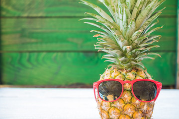 Holiday pineapple have sunglasses on green wooden background