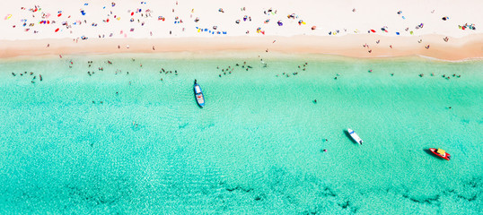 View from above, stunning aerial view of a beautiful tropical beach with white sand and turquoise clear water, long-tail boat and people sunbathing, Surin beach, Phuket, Thailand.