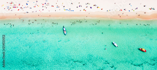 Fototapete View from above, stunning aerial view of a beautiful tropical beach with white sand and turquoise clear water, long-tail boat and people sunbathing, Surin beach, Phuket, Thailand.